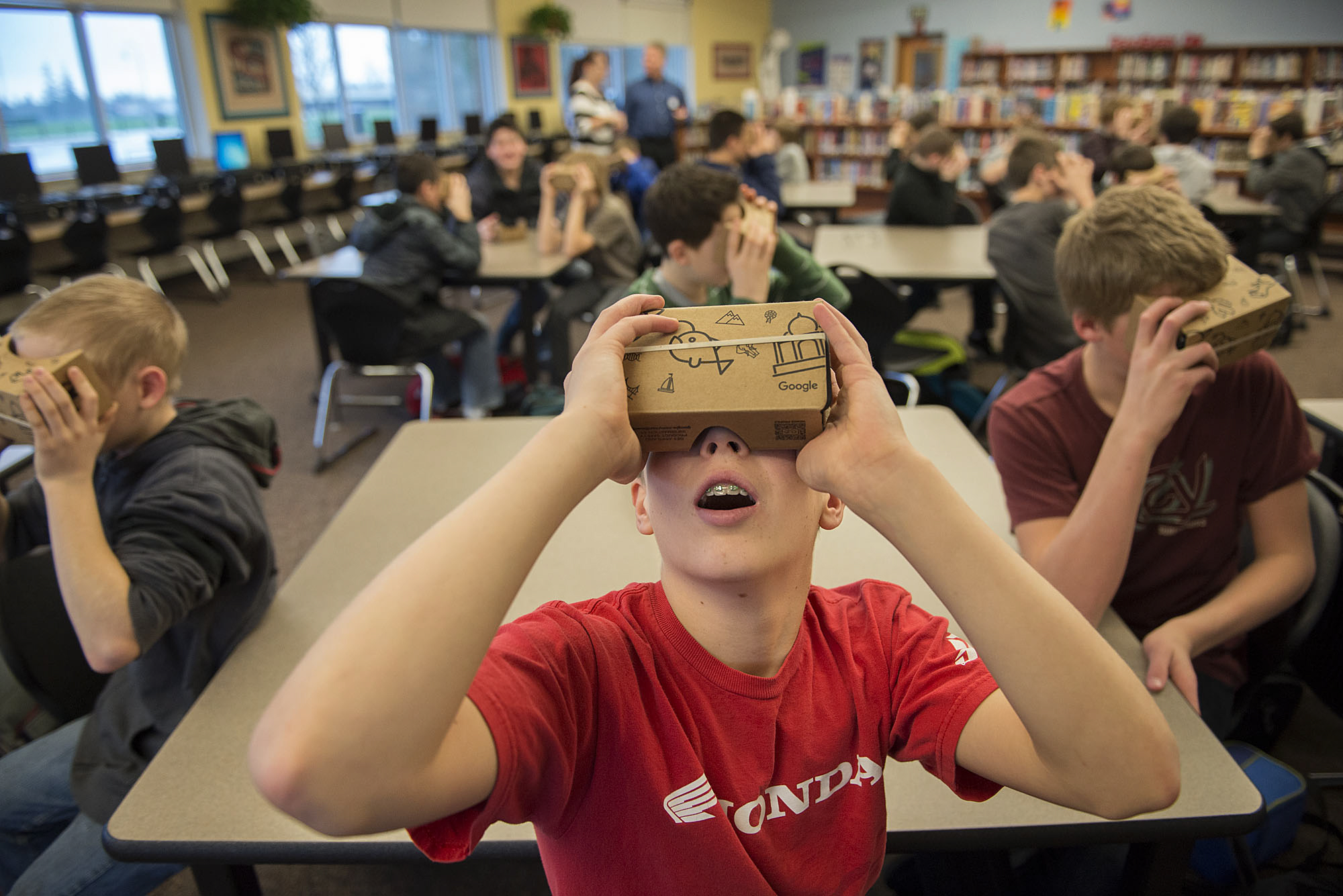 Chief Umtuch Middle School eighth-grader Jonah Muonio, 13, center, reacts while using virtual reality glasses with classmates Thursday morning, Jan. 14, 2016 in Battle Ground. (Amanda Cowan/The Columbian)