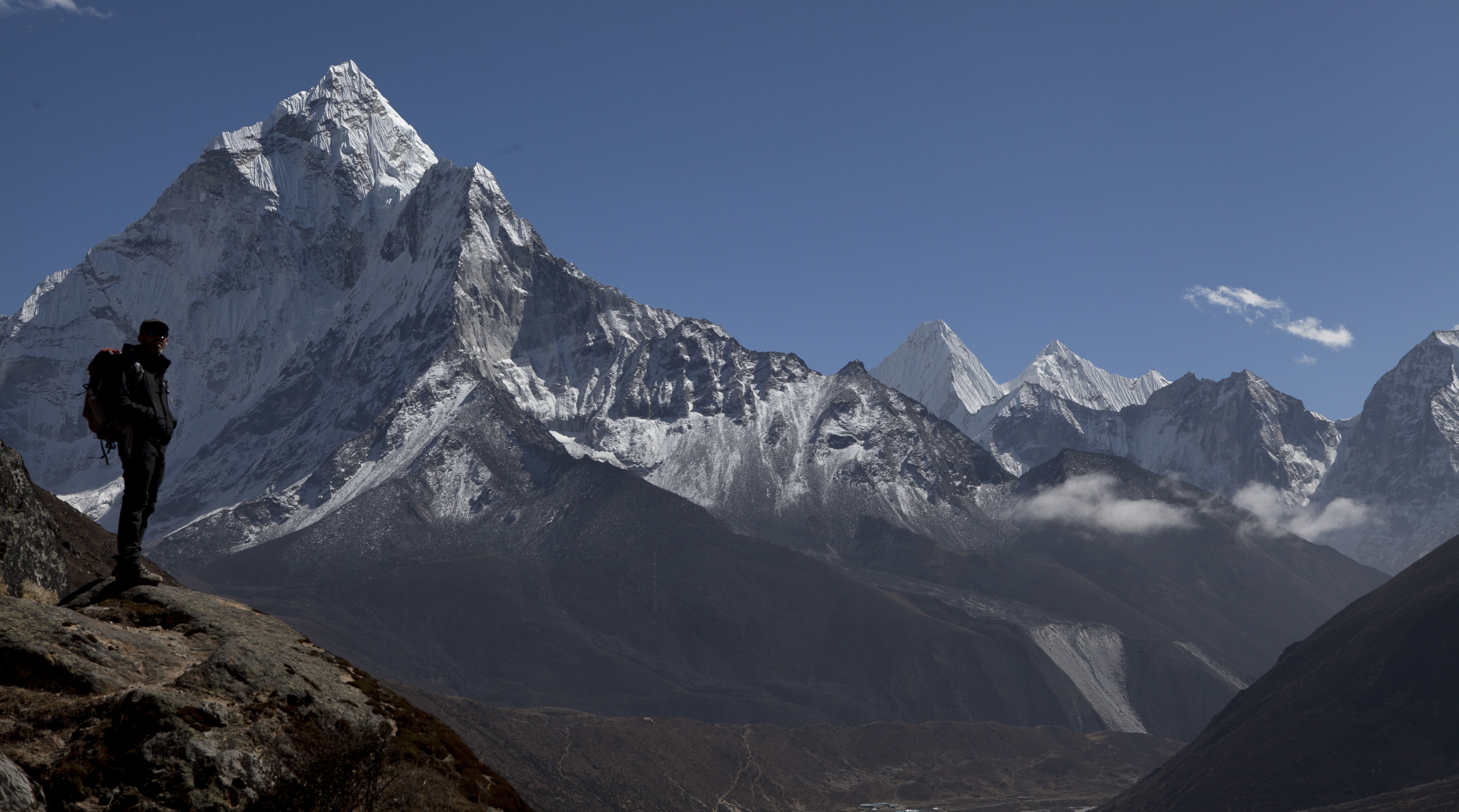 In this Sunday, Oct. 25, 2015 photo, a trekker pauses as he makes his way towards Everest Base camp, above Pheriche valley, Nepal. Earlier in August, Nepal announced the opening of Mount Everest to climbers for the first time since an earthquake-triggered avalanche in April killed 19 mountaineers and ended the popular spring climbing season. Since April's earthquake, which killed nearly 9,000 people, Nepal has been desperate to bring back the tens of thousands of tourists who enjoy trekking the country's mountain trails and climbing its Himalayan peaks. (AP Photo/Tashi Sherpa)